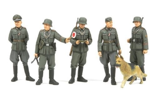 Tamiya 35320 1/35 WWII German Field Police (5 w/Dog) Most German Army divisions in WWII usually had their own field military police platoons. These units were tasked with directing traffic along routes of advance and resupply, manning checkpoints, handling prisoners as well as deserters, and maintaining law and order of captured territories. Soldiers in these field military police units were distinguished by insignia on the left sleeves of their uniforms as well as a special gorget on their chest, which led regular soldiers to derisively call them  chain dogs. Highly accurate static display model.Five figures in different poses.Illustrated instructions.Condition: Factory NewOperational Status: FunctionalThis item is brand new from the factory.Original Box: YesManufacturer: TamiyaModel Number: 35320MSRP: $22.00Category 1: Other ToysCategory 2: Model KitsAvailability: Ships in 2 Business Days!The Trainz SKU for this item is P12000536. Track: 12000536 - S01 (Shelf)  - 001 - TrainzAuctionGroup00UNK - TDIDUNK