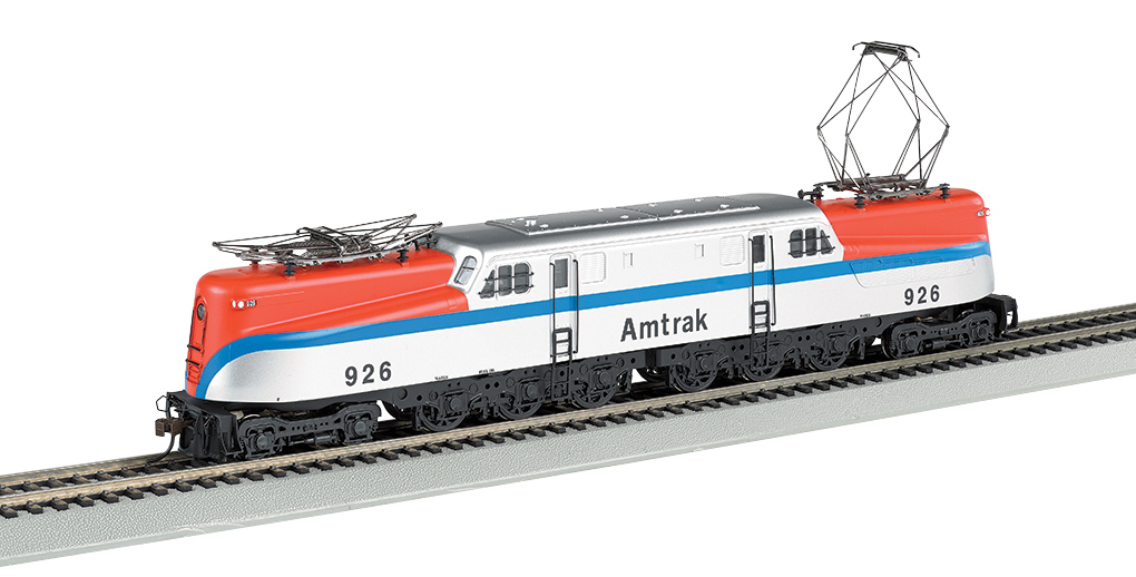 Bachmann 65207 HO Amtrak GG1 Electric - Standard DC #926 This is a Bachmann 65207 HO Scale Amtrak GG1 Electric - Standard DC #926. The electric GG-1 was introduced in the 1930s by the Pennsylvania Railroad, which needed a locomotive that could carry more rolling stock at greater speeds. Its dynamic streamlined design captured the public's imagination and made it the star of countless movies and advertisements. This DCC-ready model features include: all new tooling, die-cast frame, 12-wheel drive, twin operating metal pantographs that can be powered by overhead wire if desired, soft white LED directional headlights with dimming function, Factory-installed 8-pin socket ready for DCC decoder installation of your choice, and E-Z Mate® Mark II couplers. Performs best on 22 radius curves or greater.Condition: Factory New (C-9All original; unused; factory rubs and evidence of handling, shipping and factory test run.Standards for all toy train related accessory items apply to the visual appearance of the item and do not consider the operating functionality of the equipment.Condition and Grading Standards are subjective, at best, and are intended to act as a guide. )Operational Status: FunctionalThis item is brand new from the factory.Original Box: Yes (P-9May have store stamps and price tags. Has inner liners.)Manufacturer: BachmannModel Number: 65207Road Name: AmtrakMSRP: $235.00Scale/Era: HO ModernModel Type: Electric LocoAvailability: Ships in 1 Business Day!The Trainz SKU for this item is P12112241. Track: 12112241 - No Location Assigned - 001 - TrainzAuctionGroup00UNK - TDIDUNK