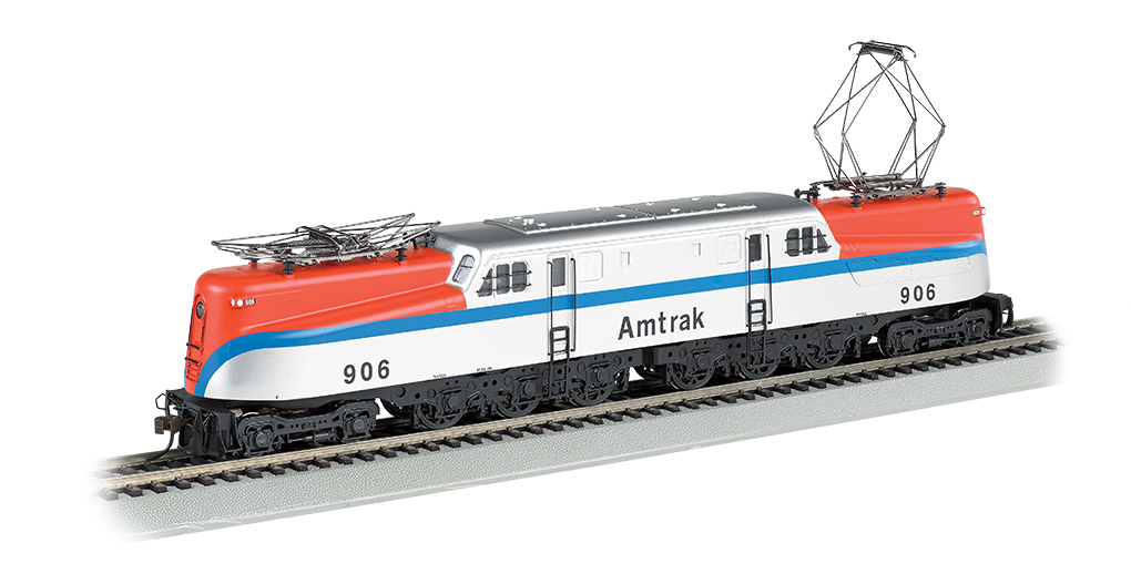 Bachmann 65306 HO Amtrak GG1 Electric with Sound & DCC #906 This is a Bachmann 65306 HO Scale Amtrak GG1 Electric with Sound & DCC #906. The electric GG-1 was introduced in the 1930s by the Pennsylvania Railroad, which needed a locomotive that could carry more rolling stock at greater speeds. Its dynamic streamlined design captured the public's imagination and made it the star of countless movies and advertisements. This DCC sound-equipped model includes our Sound Value SoundTraxx® sound package with prototypical motors with blowers, pantograph extension and retraction, air compressors, short and long horns, and bell–all in 16-bit polyphonic sound. Features include: all new tooling, die-cast frame,12-wheel drive, twin operating metal pantographs that can be powered by overhead wire if desired, soft white LED directional headlights with dimming function, and E-Z Mate® Mark II couplers. Performs best on 22 radius curves or greater.Condition: Factory New (C-9All original; unused; factory rubs and evidence of handling, shipping and factory test run.Standards for all toy train related accessory items apply to the visual appearance of the item and do not consider the operating functionality of the equipment.Condition and Grading Standards are subjective, at best, and are intended to act as a guide. )Operational Status: FunctionalThis item is brand new from the factory.Original Box: Yes (P-9May have store stamps and price tags. Has inner liners.)Manufacturer: BachmannModel Number: 65306Road Name: AmtrakMSRP: $329.00Scale/Era: HO ModernModel Type: Electric LocoAvailability: Ships in 1 Business Day!The Trainz SKU for this item is P12112239. Track: 12112239 - No Location Assigned - 001 - TrainzAuctionGroup00UNK - TDIDUNK