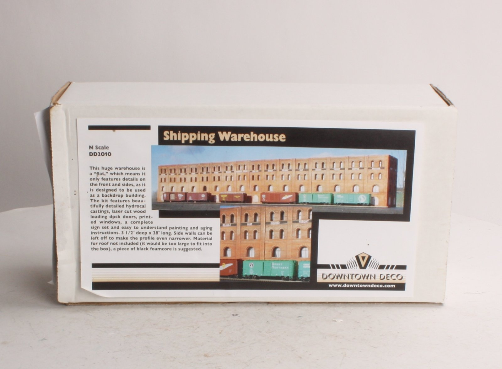 "Downtown Deco 2010 Shipping Warehouse Flat This is Downtown Deco 2010 Shipping Warehouse Flat. Based on our old ""Comet Manufacturing,""this kit has been revamped into a background flat perfect for a long string of cars. This kit has great brick detail, a new set of signs, easy-to-install printed windows and complete painting and aging instructions.Its key features are:Cast Hydrocal plaster walls, plastic door & windowsFull color paper signs and awningsEasy to understand step by step instructionsDimensions: 3-1/2 x 28 (8.9cm x 71.1cm)Condition: Factory New (C-9All original; unused; factory rubs and evidence of handling, shipping and factory test run.Standards for all toy train related accessory items apply to the visual appearance of the item and do not consider the operating functionality of the equipment.Condition and Grading Standards are subjective, at best, and are intended to act as a guide. )Operational Status: FunctionalThis item is brand new from the factory.Original Box: Yes (P-9May have store stamps and price tags. Has inner liners.)Manufacturer: Downtown DecoModel Number: 2010MSRP: $59.95Scale/Era: N ScaleModel Type: BuildingsAvailability: Ships in 1 Business Day!The Trainz SKU for this item is P11476089. Track: 11476089 - No Location Assigned - 001 - TrainzAuctionGroup00UNK - TDIDUNK"